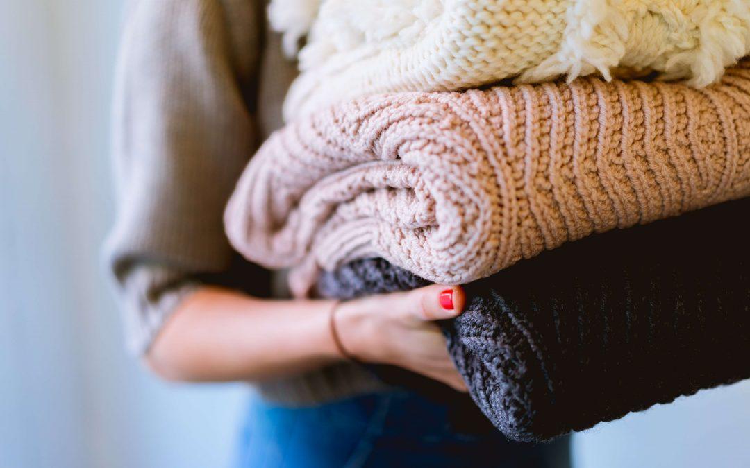 mani di donna che sorreggono alcuni maglioni ripiegati